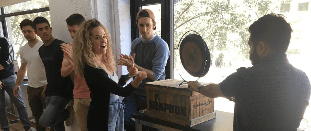 SoapBox Employee hitting a gong