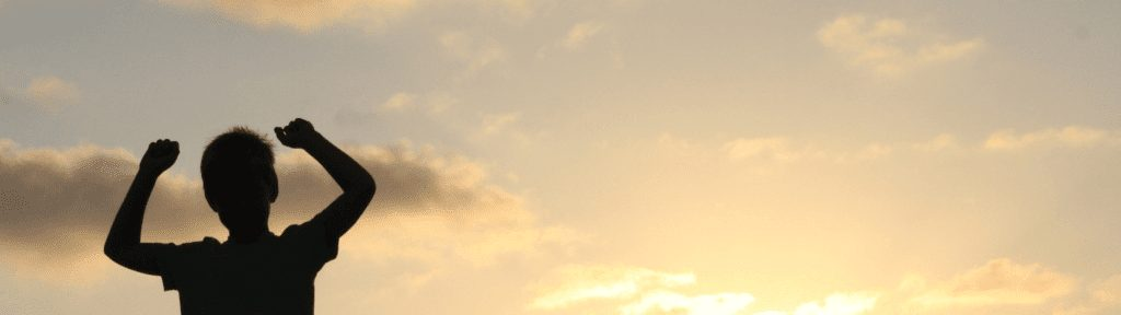 Kid cheering against sunset